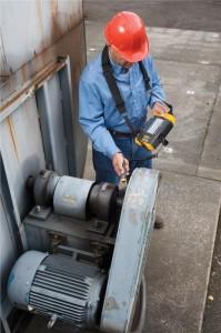 A maintenance technician uses a handheld Fluke 810 Vibration Tester on a belt-driven fan setup.