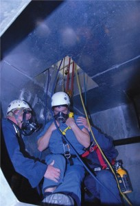 Two rescuers have located the victim and pulled him to a spot beneath the roof hatch. While attaching the haul system to his harness, they must also keep their own air hoses and lifelines from tangling. So far, the rescue has taken about 20 minutes. The tasks are realistic, completely absorbing and quite strenuous. Photo: Carroll McCormick